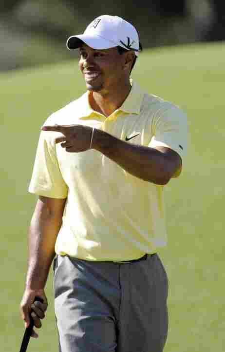 Tiger Woods pointing to the crowd during a Masters practice round.