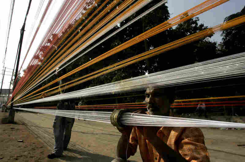 Workers prepare threads for kite flying in anticipation of the Hindu festival of Sankrant in Amritsar, India.