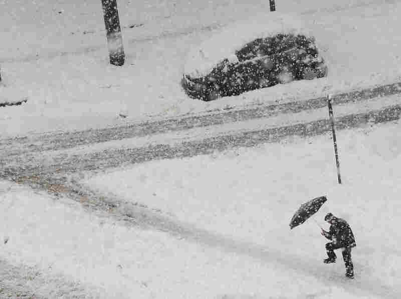 A man walks during a heavy snowfall in Milan, Italy.