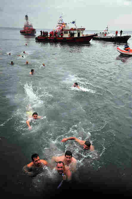 Orthodox Christians in Thessaloniki, Greece, race to retrieve a cross as part of an Epiphany ceremony to bless the water.