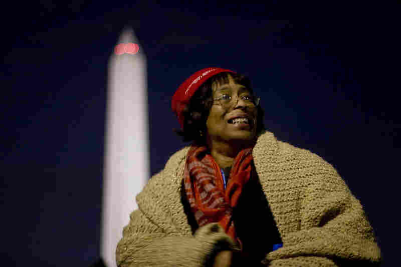 Jacklyn Ireland, an official inauguration volunteer from Baltimore, Md., greets the hundreds of people pouring onto the National Mall before sunrise.