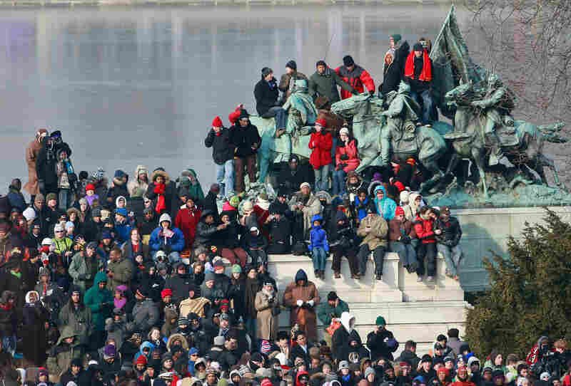 The growing crowd piles on top of a statue outside of the National Mall.