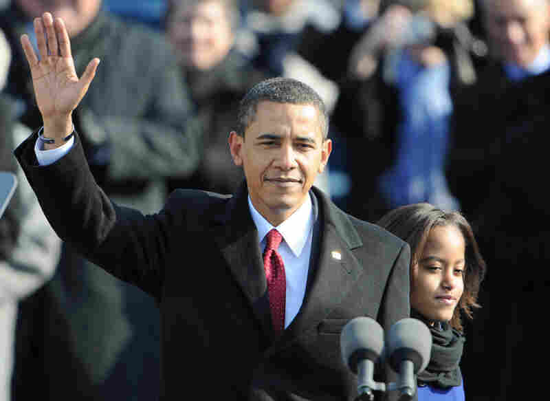 President Obama waves after being sworn in, with his daughter Malia by his side.