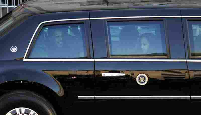 The Obama family looks out of their official limousine following the inaugural swearing-in ceremony.