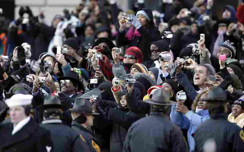 The crowd attempts to capture a photo of President Barack Obama as he walks by during the inaugural parade.