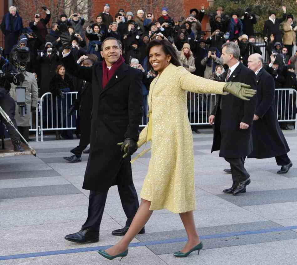 President Barack Obama and first lady Michelle wave to parade goers lining Pennsylvania Ave.