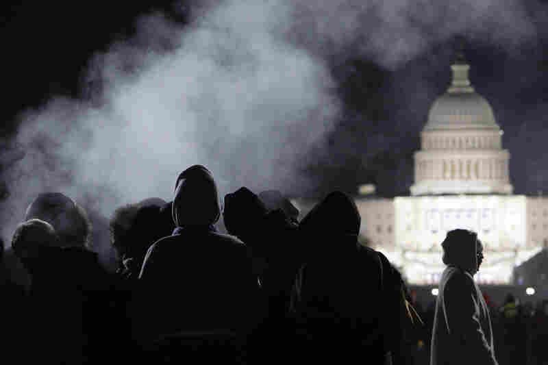 People attempt to stay warm on the National Mall as they wait for sunrise on the morning of the inauguration.
