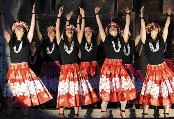 "As inauguration attendees shiver in Washington, D.C., a group of ""Obama Girls"" in the city of Obama, Japan, perform a Hawaiian hula dance at a Buddhist temple."
