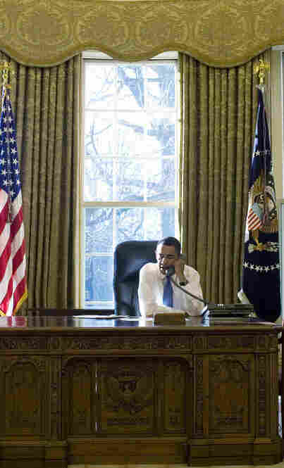 The president makes his morning phone calls from the Oval Office.