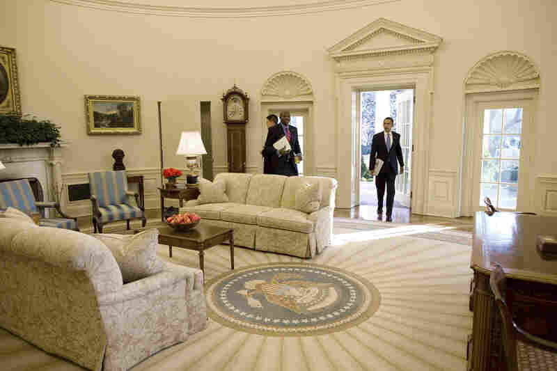Barack Obama enters the White House Oval Office for the first time as president.