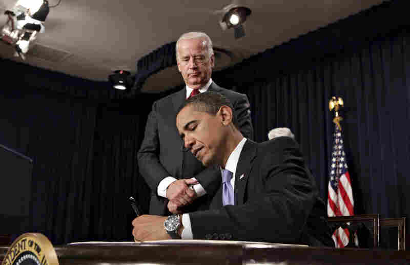 Biden looks on as the president signs executive orders during a meeting with their senior staff.