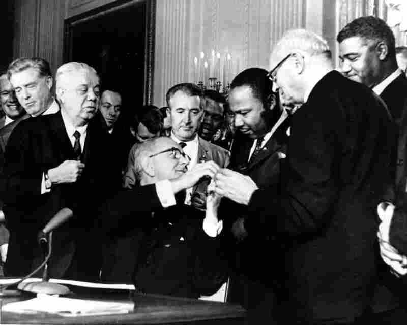 President Lyndon B. Johnson extends his hand to the Rev. Martin Luther King Jr. after presenting King with one of the 72 pens used to sign the ground-breaking Civil Rights Act of 1964.  The legislation effectively outlawed racial segregation in schools, public places and employment.