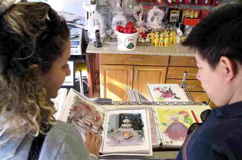 Customers like Laura and Hugo Bernal peruse pictures of the bakery's many cakes for.  They will be celebrating their daugher's 15th birthday.
