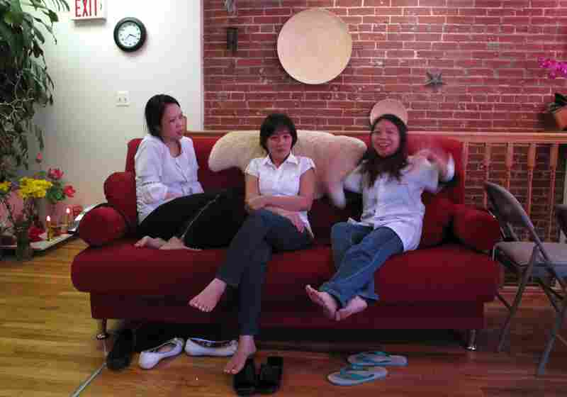 The girls sit on the couch, chatting, laughing, and waiting for customers.