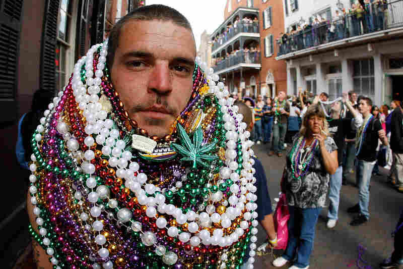 A reveler sports a Mardi Gras bead collection on New Orleans' Bourbon Street.