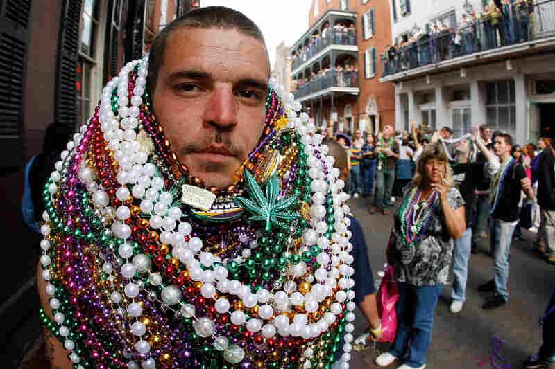 A reveler sports a Mardi Gras bead collection on New Orleans' Bourbon Street.