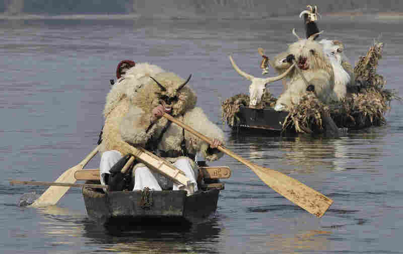 Costumed men cross the Danube before marching through the streets of Mohacs, Hungary. Such carnival festivities date to the 16th-century Ottoman occupation of Hungary, when Mohacs residents dressed in sheepskin to frighten off Turkish invaders.