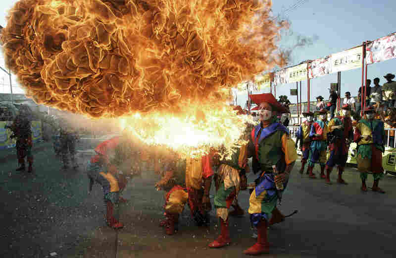 "A fire-breathing reveler heats up the celebration in Barranquilla, Colombia. In 2003, UNESCO declared this carnival a ""masterpiece of oral and intangible heritage of humanity."" Introduced by Spaniards, it has incorporated elements of indigenous culture."