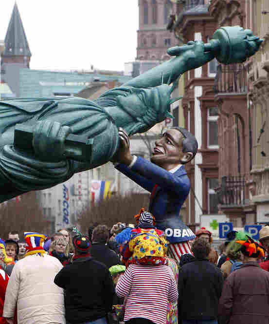 In Mainz, German, a carnival float depicts President Obama propping up Lady Liberty.