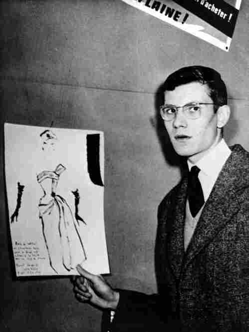 Yves Saint Laurent holds up a drawing of the cocktail-dress design that won him first prize in a 1953 fashion drawing competition in Paris. His success in the contest led to his job with the Christian Dior team of designers.