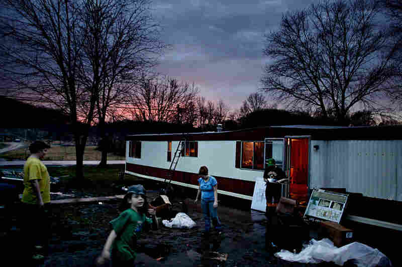 The Goins family moves their belongings into a new trailer as dusk settles over the town of Chauncey.  Communities that once struggled to get by can no longer make ends meet after the economic downturn in the United States.