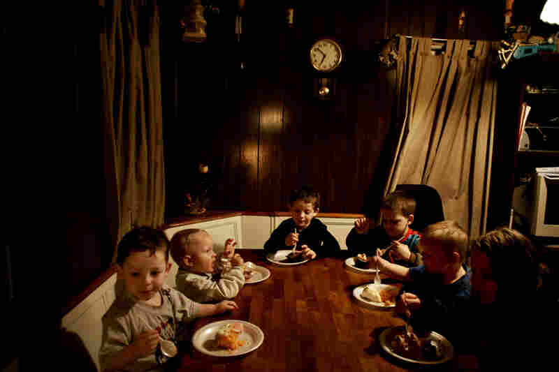 The Goins children circle around the table for dinner. T he extended family occupies the corner of a street in Chauncey, spread out between a trailer home and a house. The trailer home has no running water so everyone gathers in the house to eat and bathe.