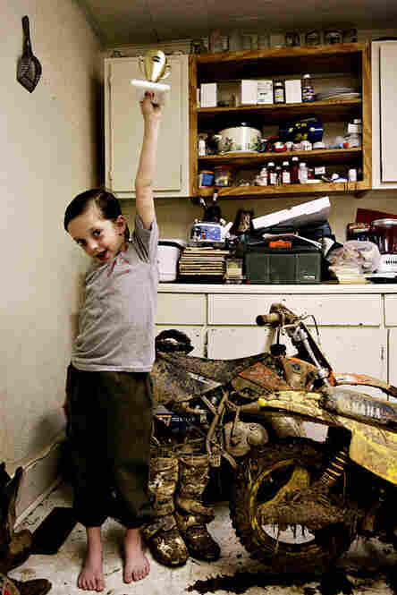 Jesse Sellers Jr., his hair still wet from a bath, stands in his kitchen holding a trophy he won during his first dirt bike competition.