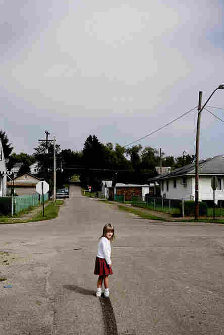 Lacey Sellers wanders out in the middle of the street near their home in Chauncey to examine the skid mark her father left as he drove away.