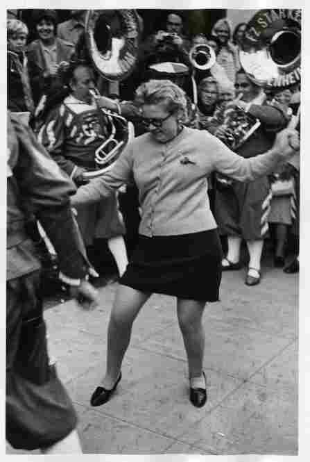 A woman enjoys the music of a brass band and the liberty afforded by a miniskirt in New York City, 1972. Image courtesy George Eastman House Collection