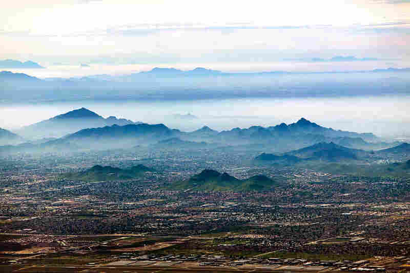 "Smog settles between hills north of downtown Phoenix. In the Phoenix metropolitan area, the natural inversion layer traps rising particulates and forms ""brown cloud"" as the ground heats up during the day. Smog affects inhabitants of urban populations who already suffer from respiratory ailments, and continued suburban growth contributes to declining air quality."
