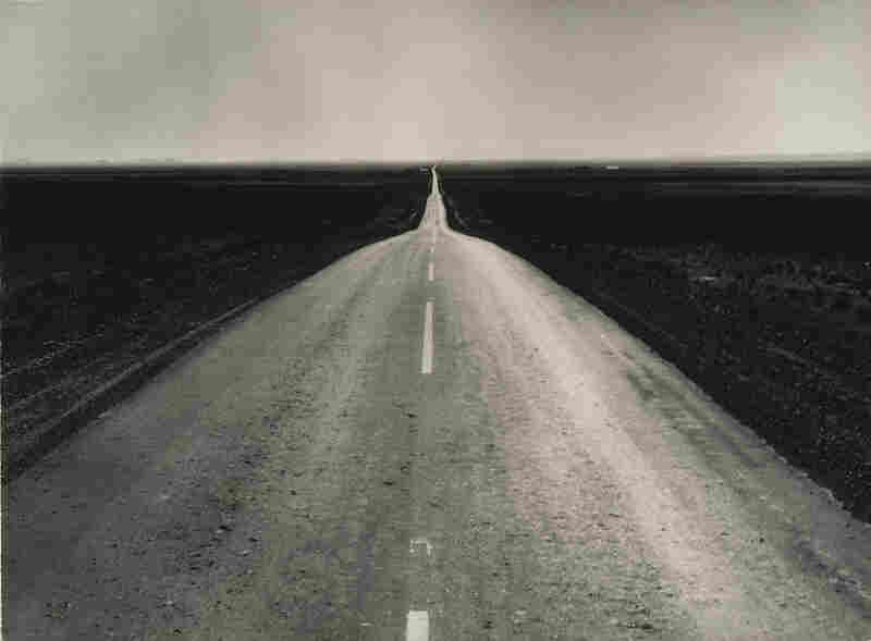 The Road West, New Mexico, 1938Dorothea Lange, 1895-1965, is one of the better-known names in the world of photography.  Best known for her Depression-era photojournalism, she took this photograph of U.S. 54, a route often taken by families seeking work in California.  Even today its invitation to the proverbial American road trip remains relevant. (Gelatin silver print, courtesy The Mus...