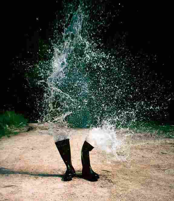 """Roman Signer is a Swiss photographer whose art also spans sculpture and video, covering nearly 30 years.  """"For Water Boots, he says, """"I filled two black boots with water and put a small amount of explosive in them."""" Wasserstiefel (Water Boots), 1986, Weissbad, Appenzell, Switzerland"""