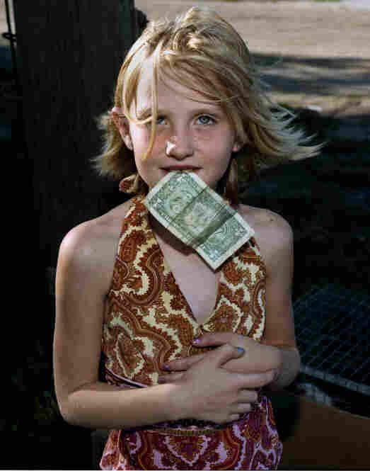 Girl with dollar bill, Kansas, by Larry Schwarm