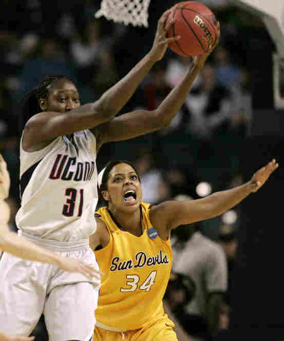 Tina Charles (left) led the Huskies through their undefeated season.  In a regional final against Arizona State, she grabs a pass while covered by Lauren Lacey.