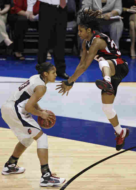 Maya Moore (left) dodges Louisville's leaping Angel McCoughtry as she heads toward the basket.  Moore added 18 points to the Huskies' final score.