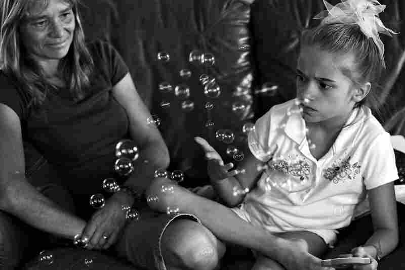 """Diane Lierow watches her daughter, Dani, play with bubbles, which is a part of her physical therapy. """"Ever since the first day we had her in our home, she felt like she was my own child,"""" Lierow said."""