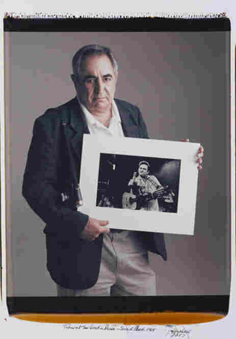 Jim Marshall holds an image of Johnny Cash, taken at San Quentin Prison during a 1969 sound check. According to Marshall, the gesture was made in jest, but it has become one of the most memorable images of Johnny Cash.