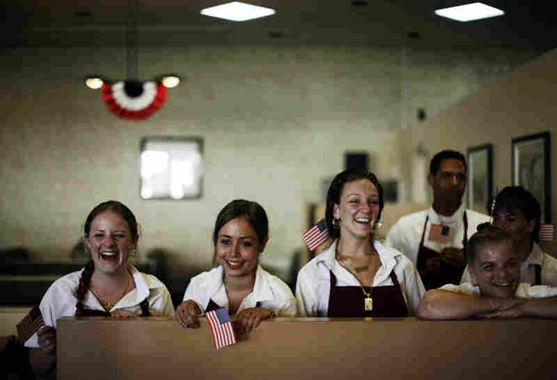 The serving staff watches from the back as Obama greets customers and workers at the Deli Den in Fort Lauderdale, Fla.
