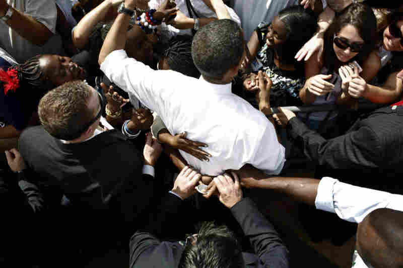 Secret Service agents tug at the hands of a supporter as she hugs Obama at Legends Field in Tampa, Fla.