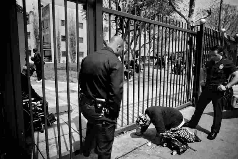 Los Angeles police officers ask a homeless woman to get up. People can be ticketed for lying on the street past 6 a.m.