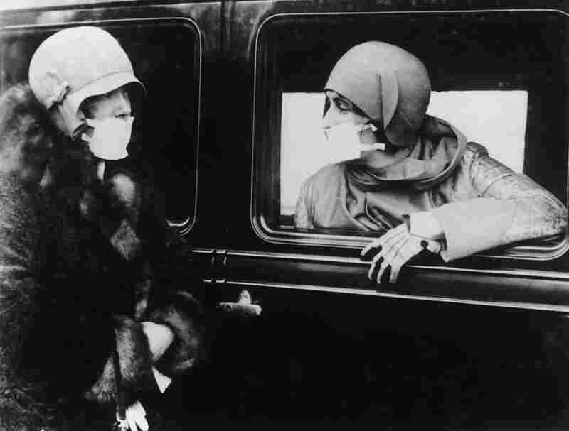 The masks became something of a fashion statement, as demonstrated by these comfortably clothed women, still determined to have a chat despite their covered mouths.