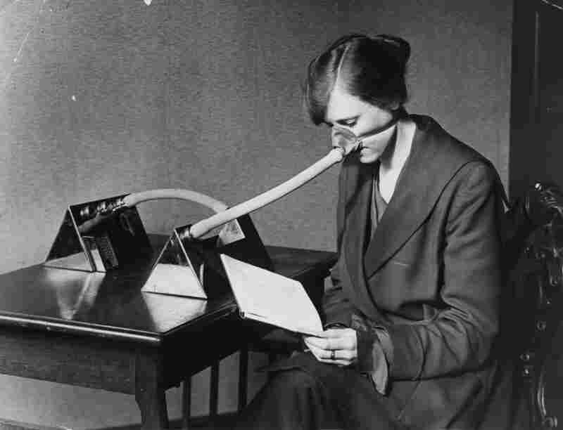 "In 1919, a woman wears what was most likely considered the ""flu mask of the future"" — a contraption bizarrely elephantine in appearance — so comfortable you can read while wearing it!"