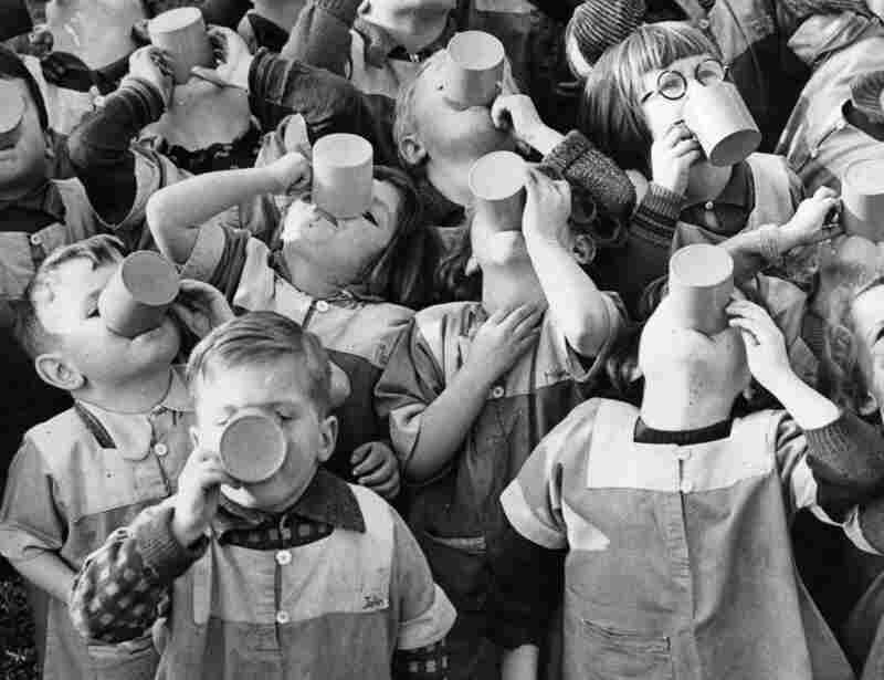 In 1938, nursery school children in Swansea, Wales, appear to have missed the point of gargling, as they empty their cups.