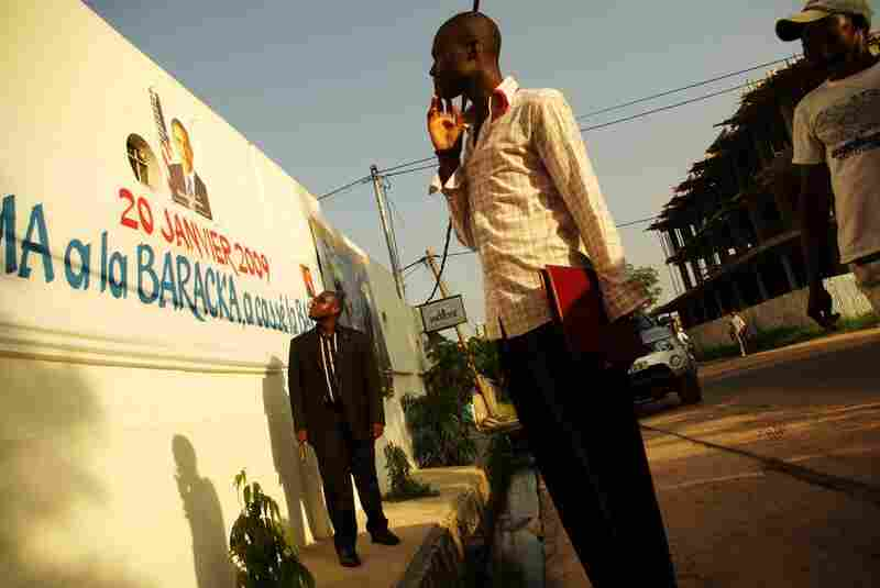 Passers-by look at a banner of Barack Obama in Brazzaville, Republic of Congo.