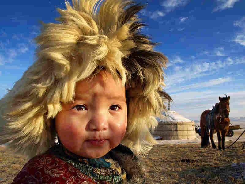 A child looks into the distance under a bright morning sky in Inner Mongolia, China.