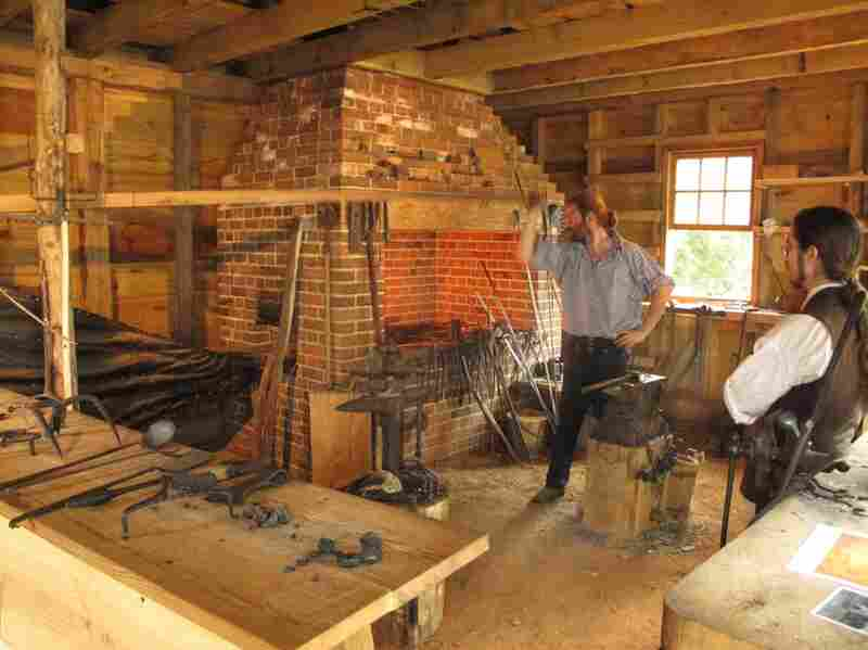 Zieg stokes the fire using a large handmade bellows.