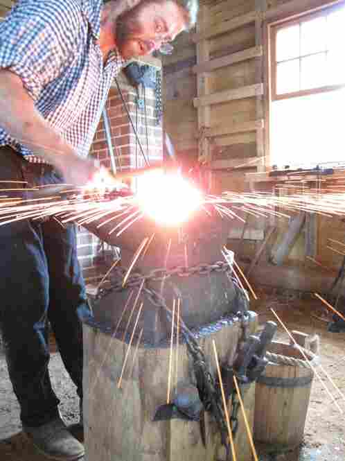 Sparks fly as Zieg hammers the steel. He's making a scythe.