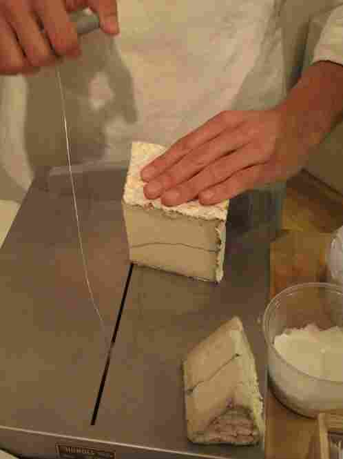 Using a wire cutter to slice Humboldt Fog goat cheese, made with a vein of vegtable ash.