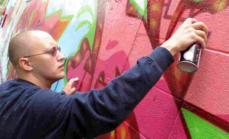 """Corey Stowers is the art director for Words, Beats & Life. On hIs section of the mural, he writes """"Dad""""-- his graffiti name ever since he became a father."""