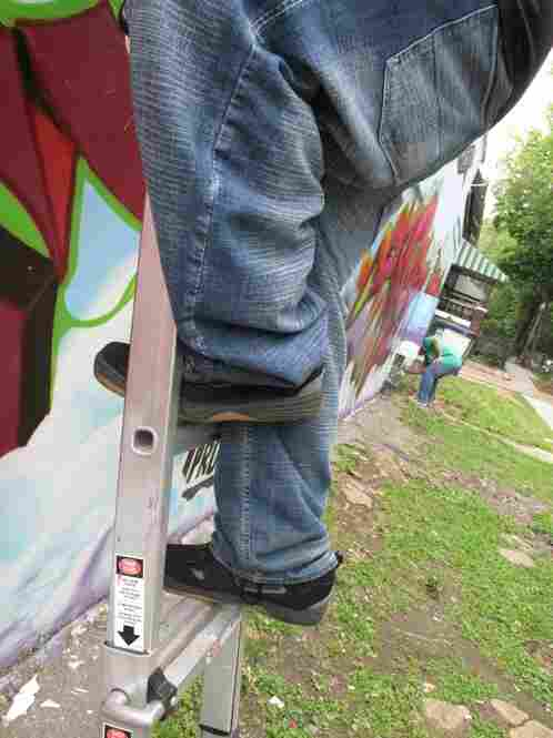 Creating graffiti murals often has an element of danger. Try climbing a ladder with baggy pants, like 19-year old Matas Yongvongpaibul.